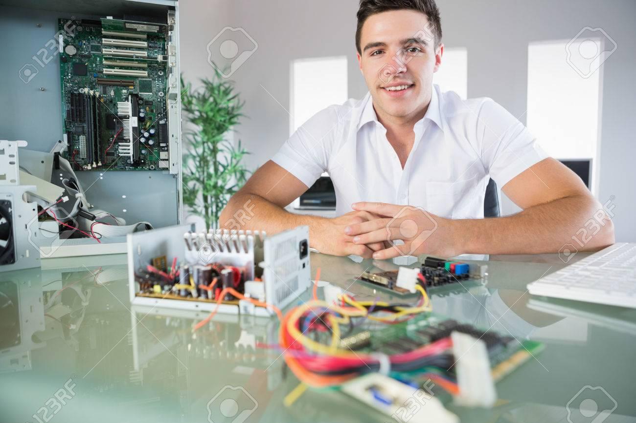 Ingénieur en informatique attrayant assis à son bureau en souriant