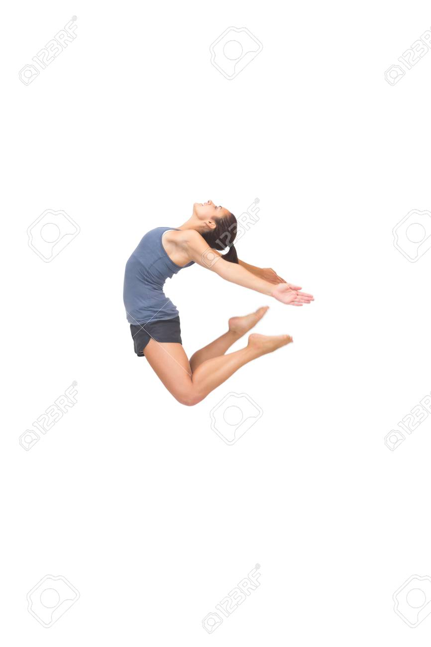 7babc4753b94 Flexible sporty brunette jumping in the air on white background Stock Photo  - 26743393