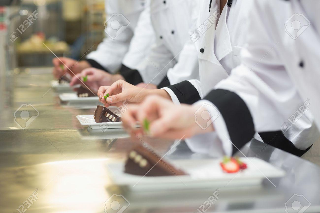 Busy Kitchen team of chefs garnishing dessert plates in a busy kitchen stock