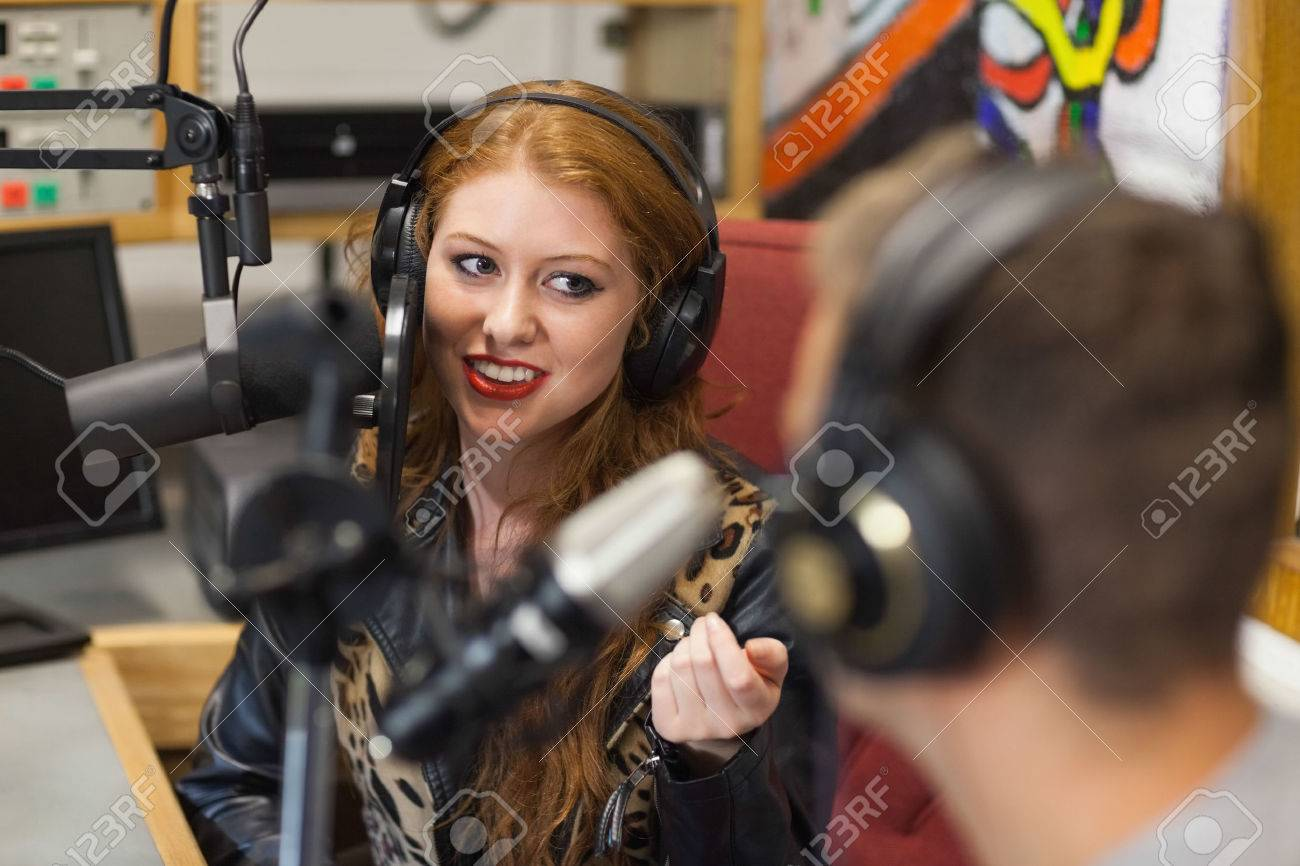 Attractive happy radio host interviewing a guest in studio at college - 25779157