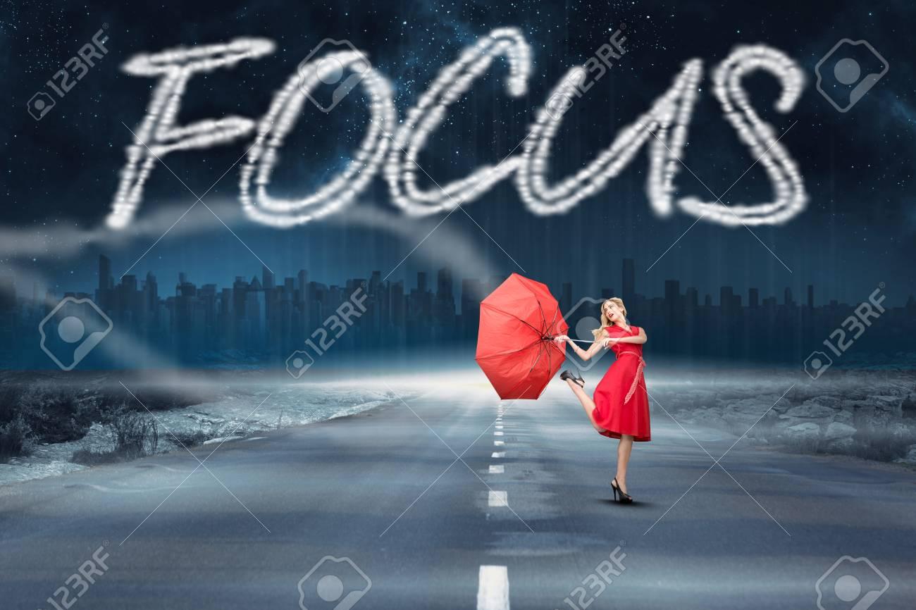Das Wort Fokus und schöne Frau posiert mit einem kaputten Regenschirm gegen  Straße, die bis zum Horizont