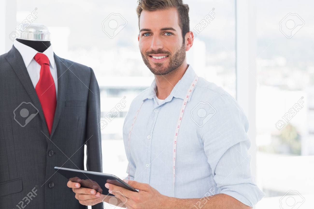 Portrait of a young male fashion designer with digital tablet by suit on dummy in the studio Stock Photo - 27073799