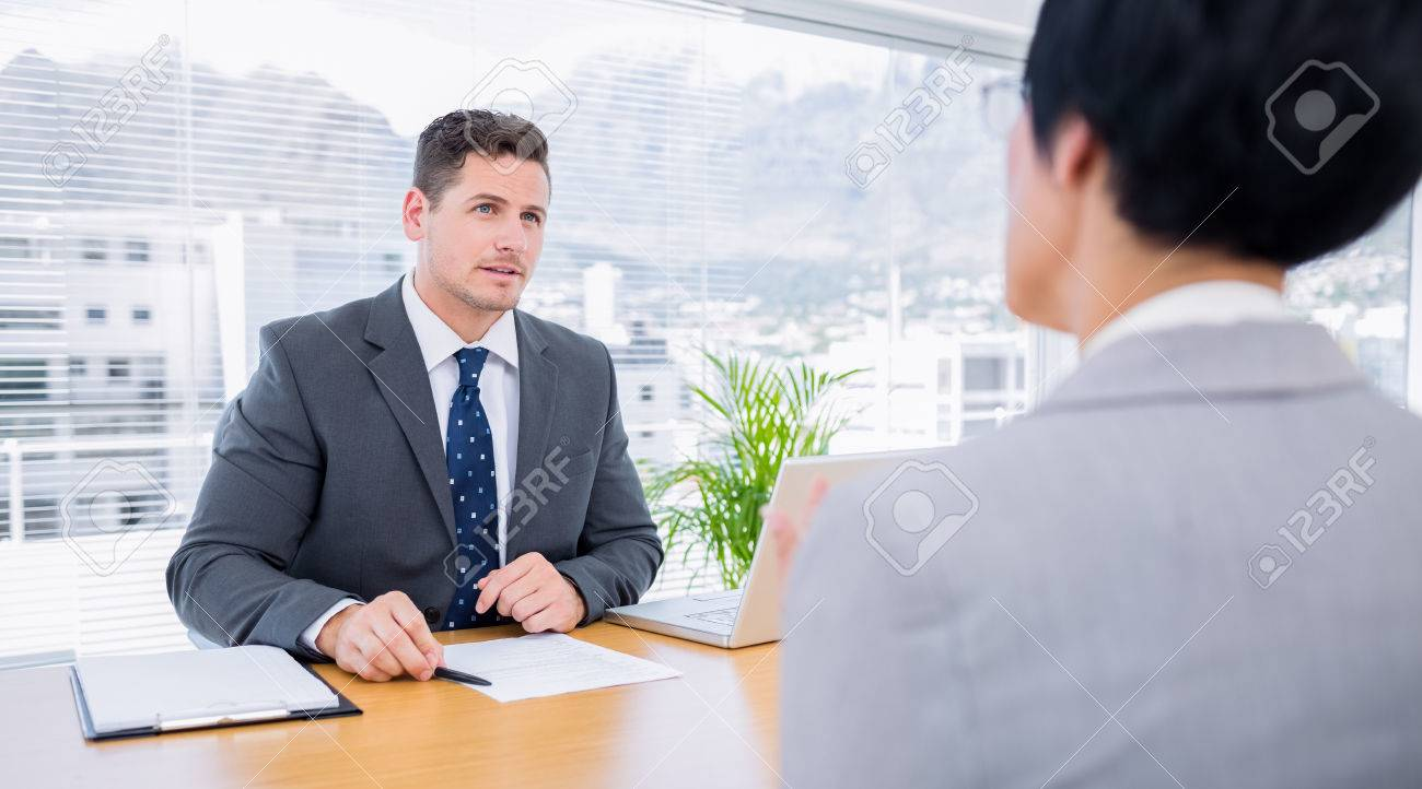 male recruiter checking the candidate during a job interview male recruiter checking the candidate during a job interview at office stock photo 27080276