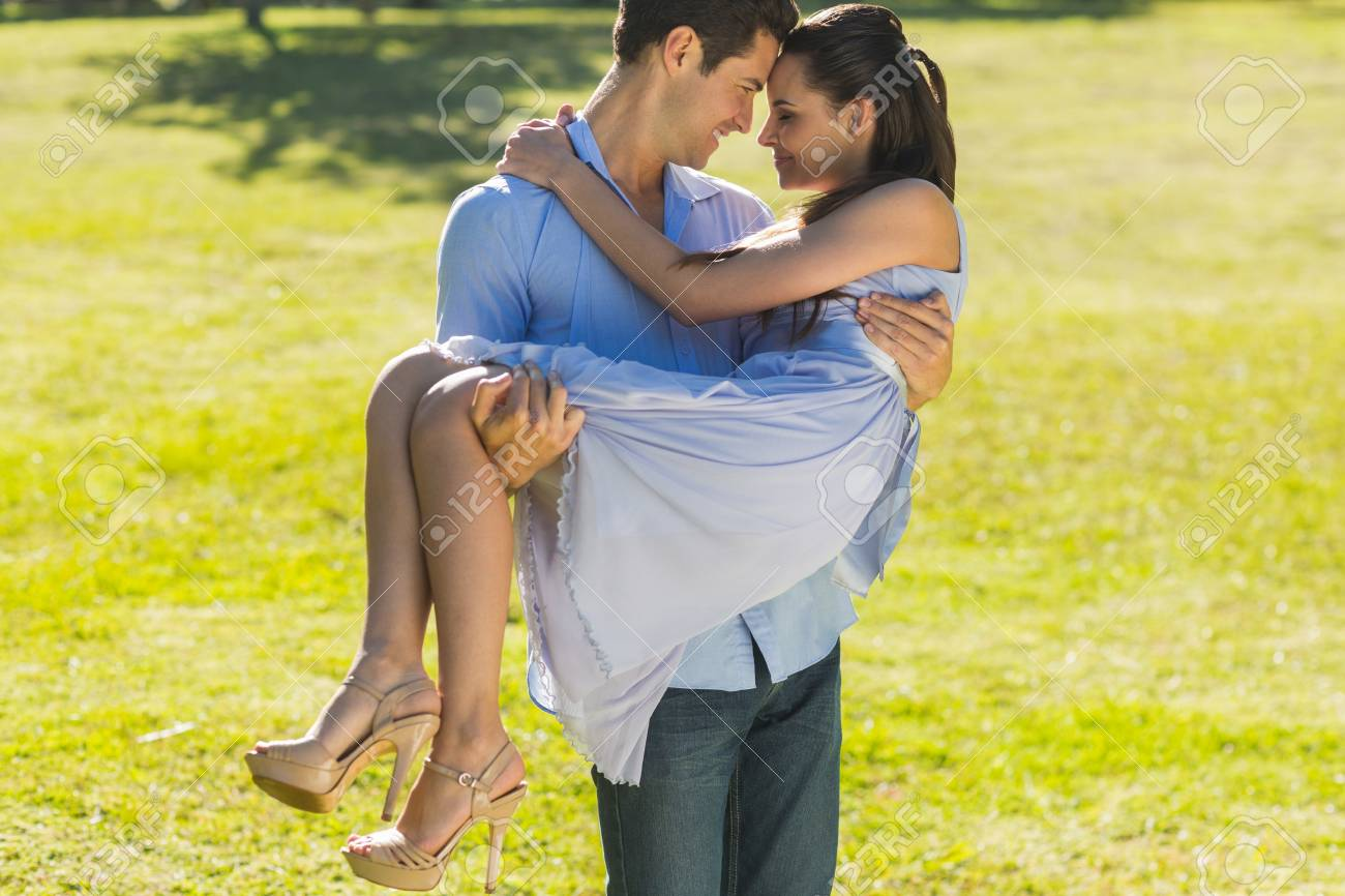 Young man carrying a beautiful woman in the park Stock Photo - 27116090