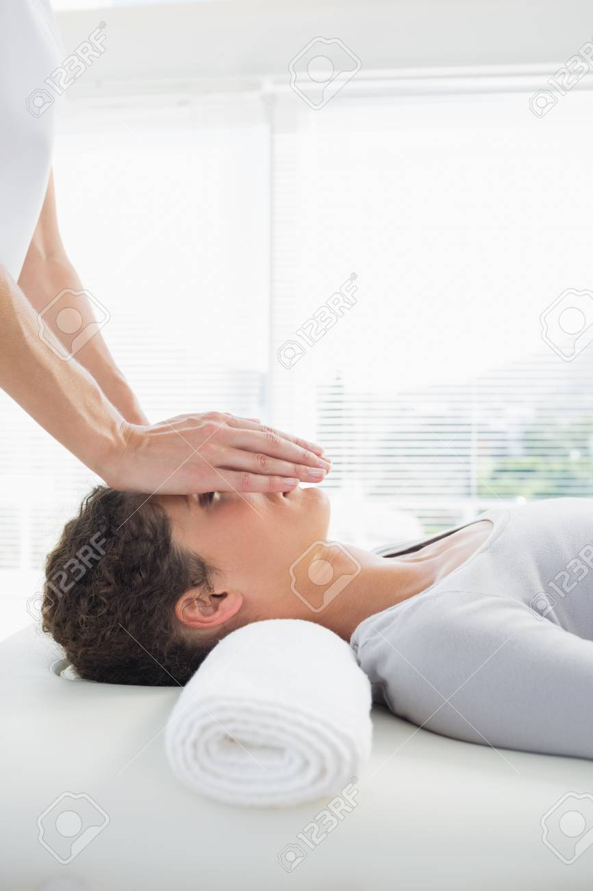 Beautiful young woman having reiki treatment over face in health spa Stock Photo - 27120220