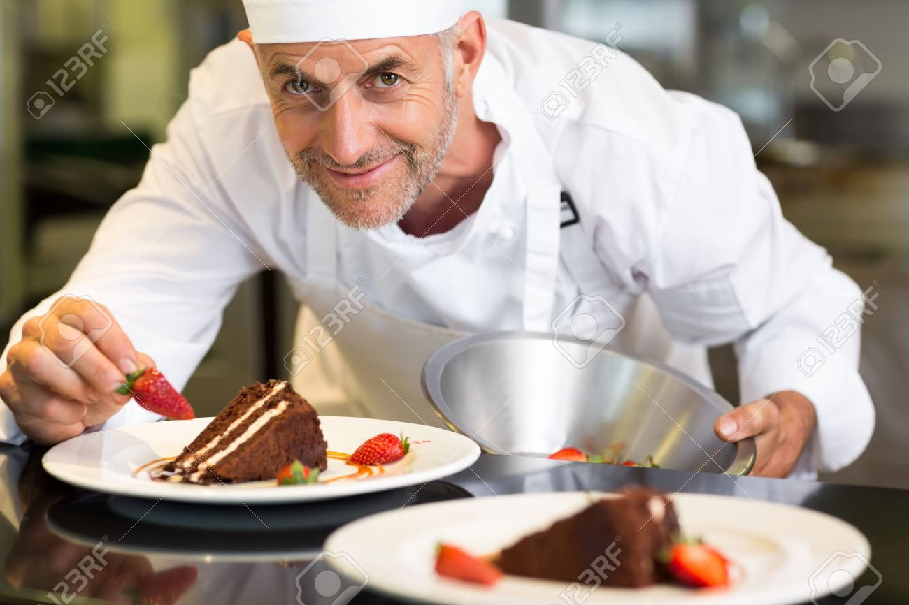 Closeup Portrait Of A Smiling Male Pastry Chef Decorating Dessert ...