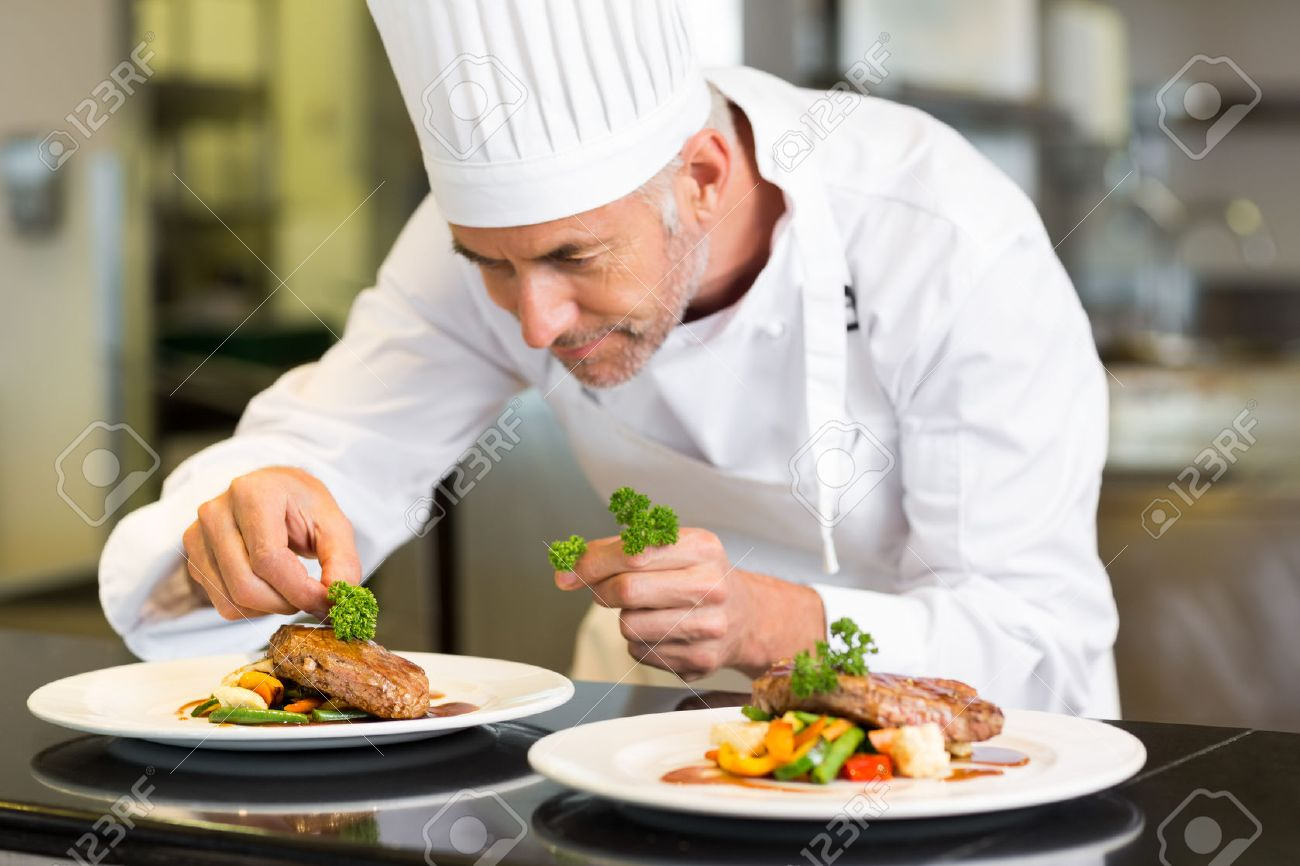 Closeup of a concentrated male chef garnishing food in the kitchen stock photo 27150722