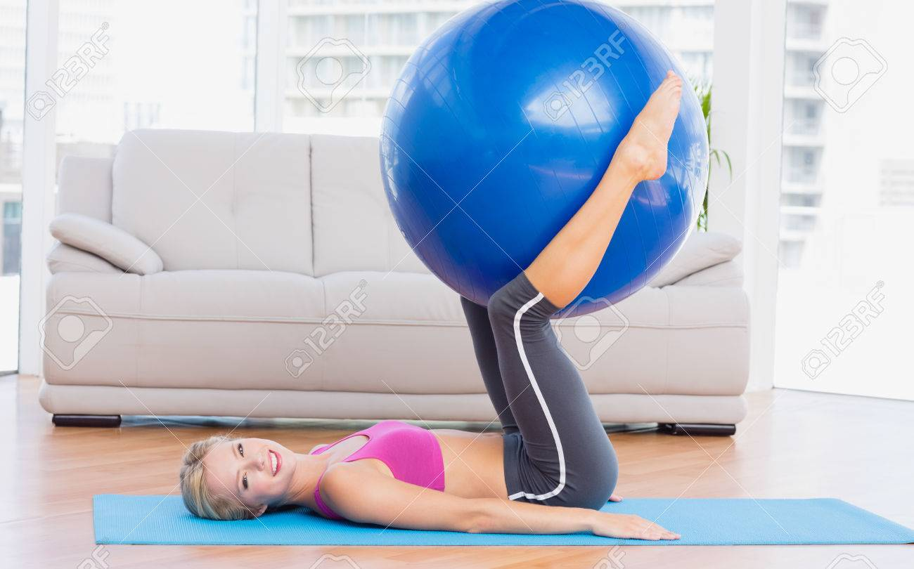Slim Blonde Holding Exercise Ball Between Legs At Home In The Living Room Stock Photo