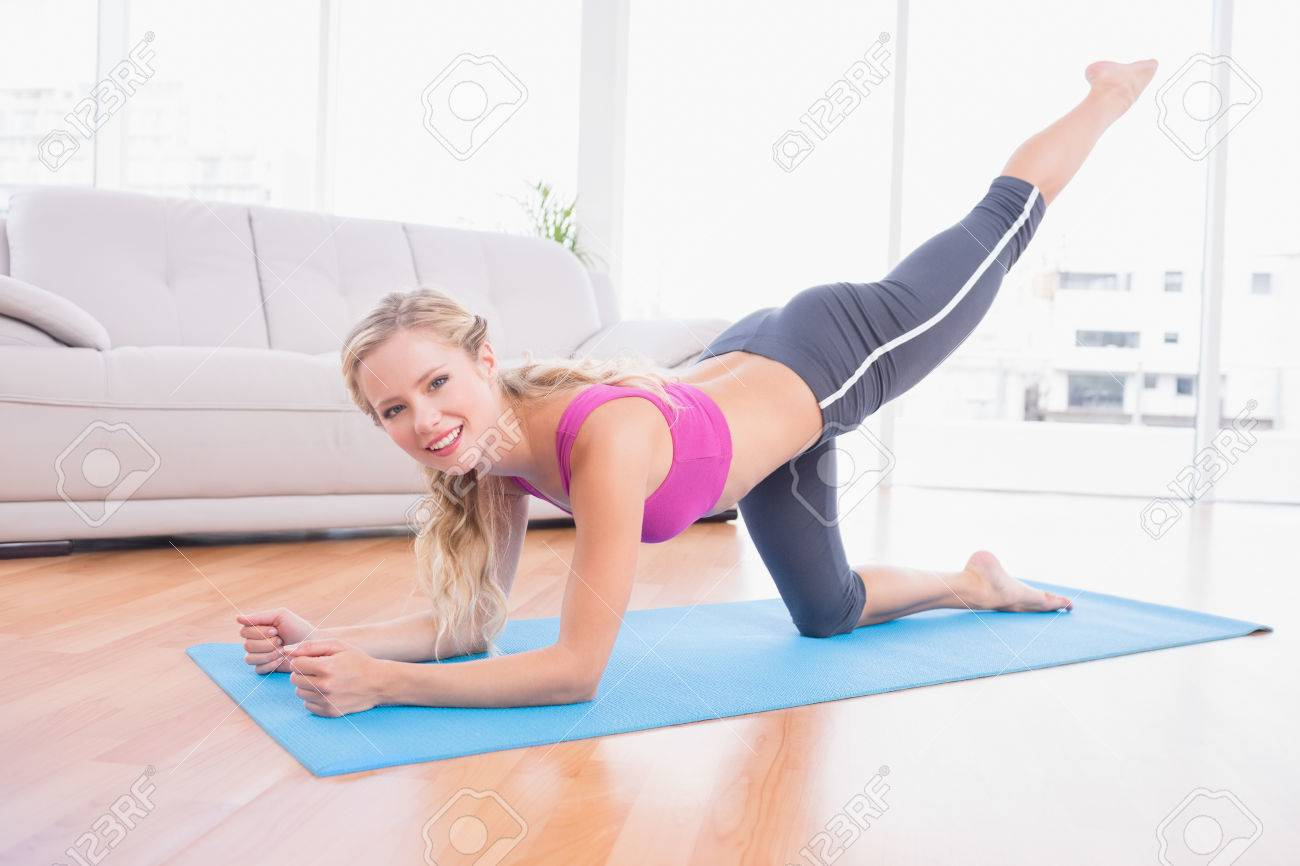 Toned Blonde Doing Pilates On Exercise Mat Smiling At Camera Home In The Living Room