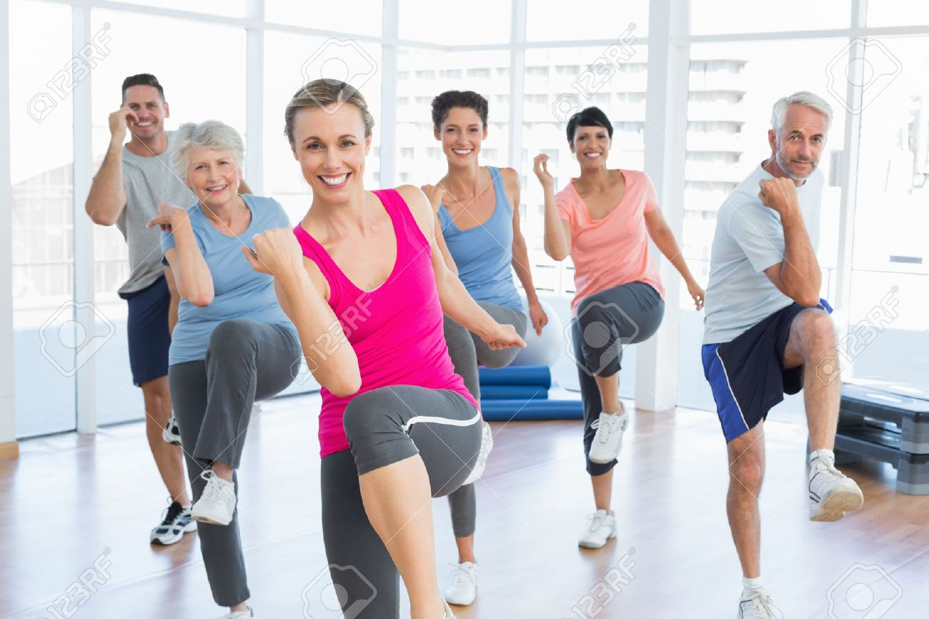 Portrait of smiling people doing power fitness exercise at yoga class in fitness studio - 27209278