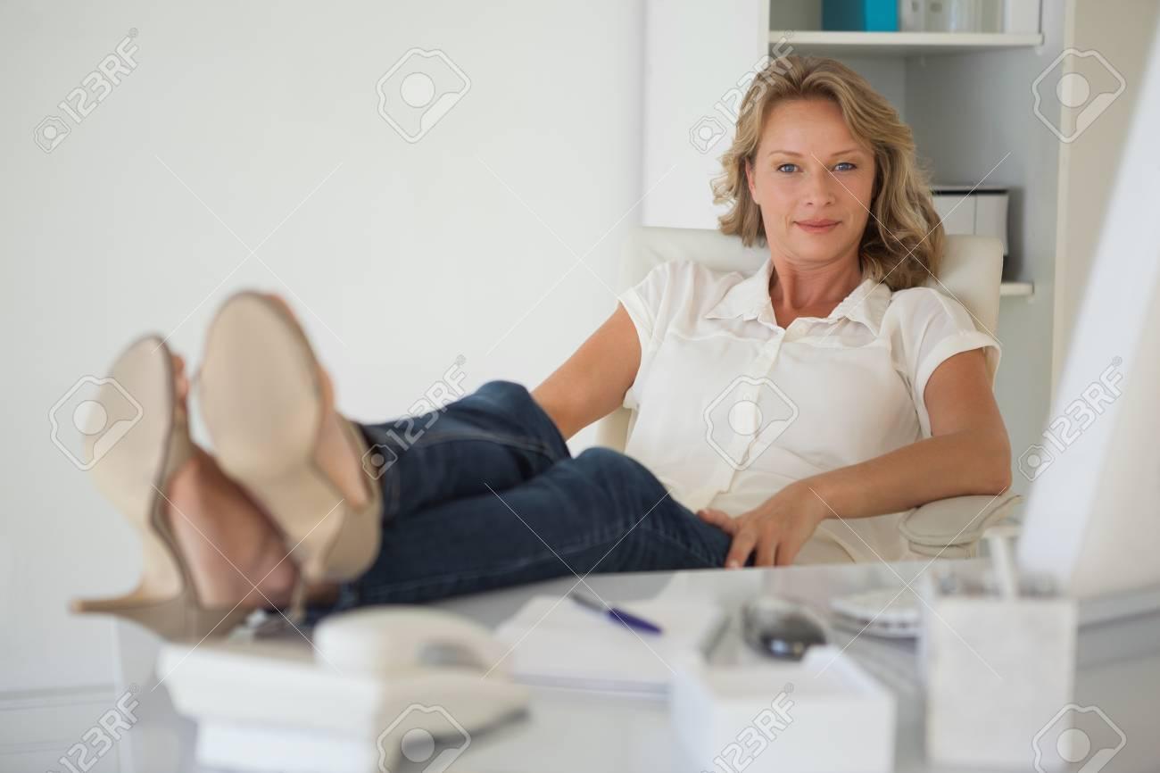 Dans sa affaires décontractés assis à son bureau avec les pieds