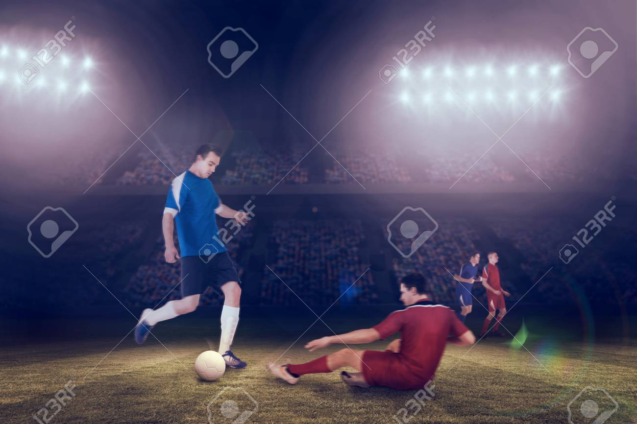 Football players tackling for the ball against large football stadium under blue sky Stock Photo - 29046904