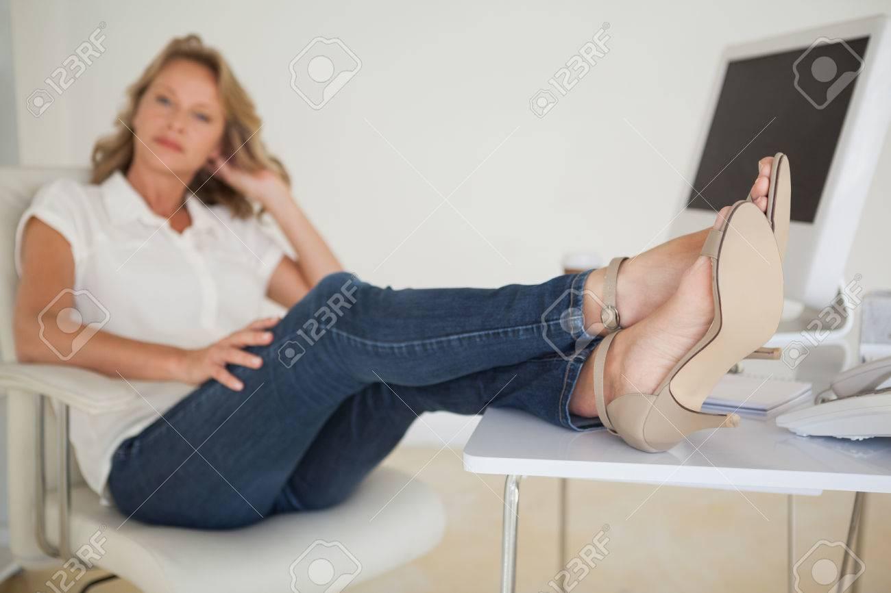 D affaires décontractée assis à son bureau avec les pieds dans son