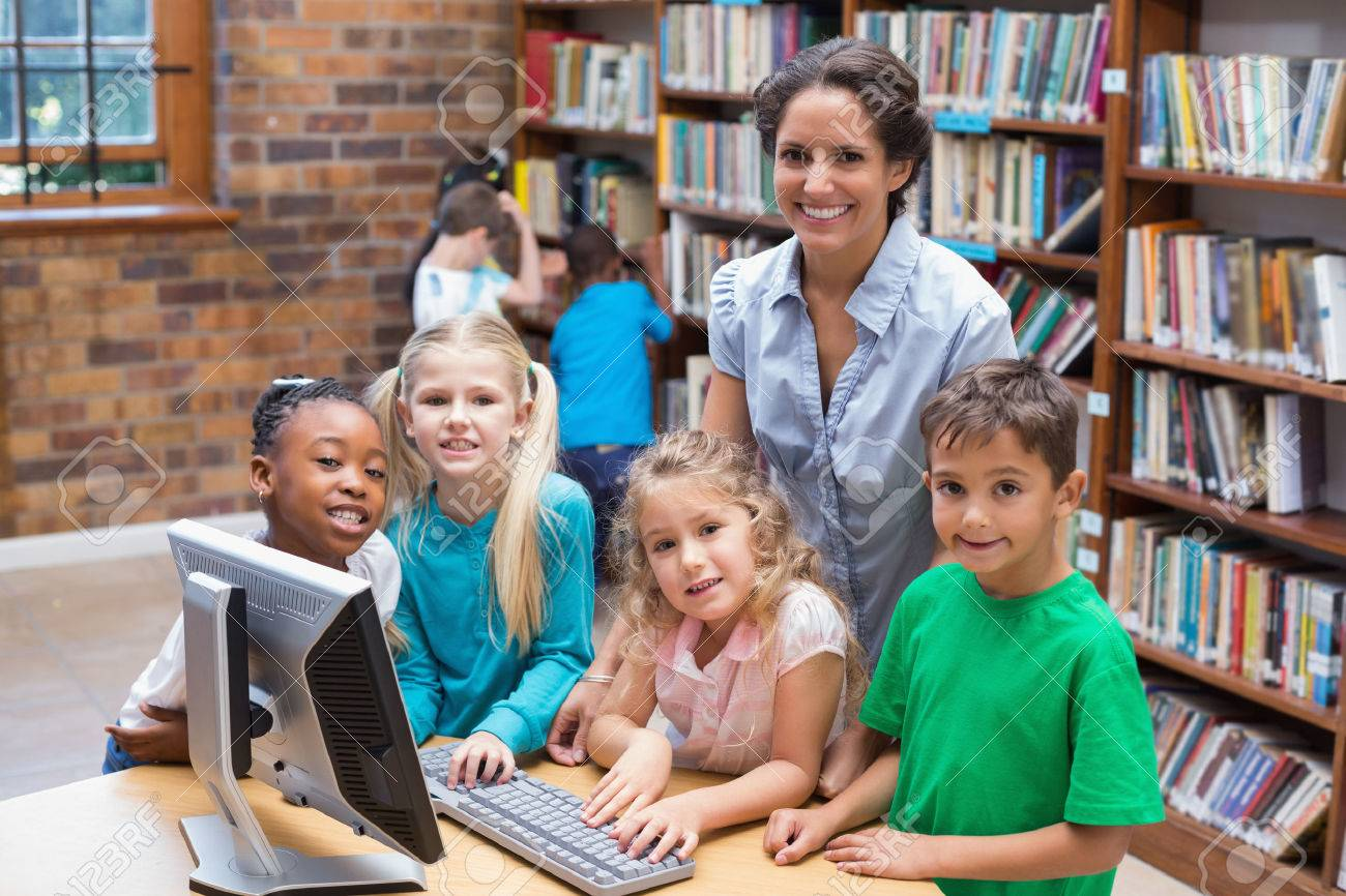 Cute pupils and teacher looking at computer in library at the elementary school - 30861862
