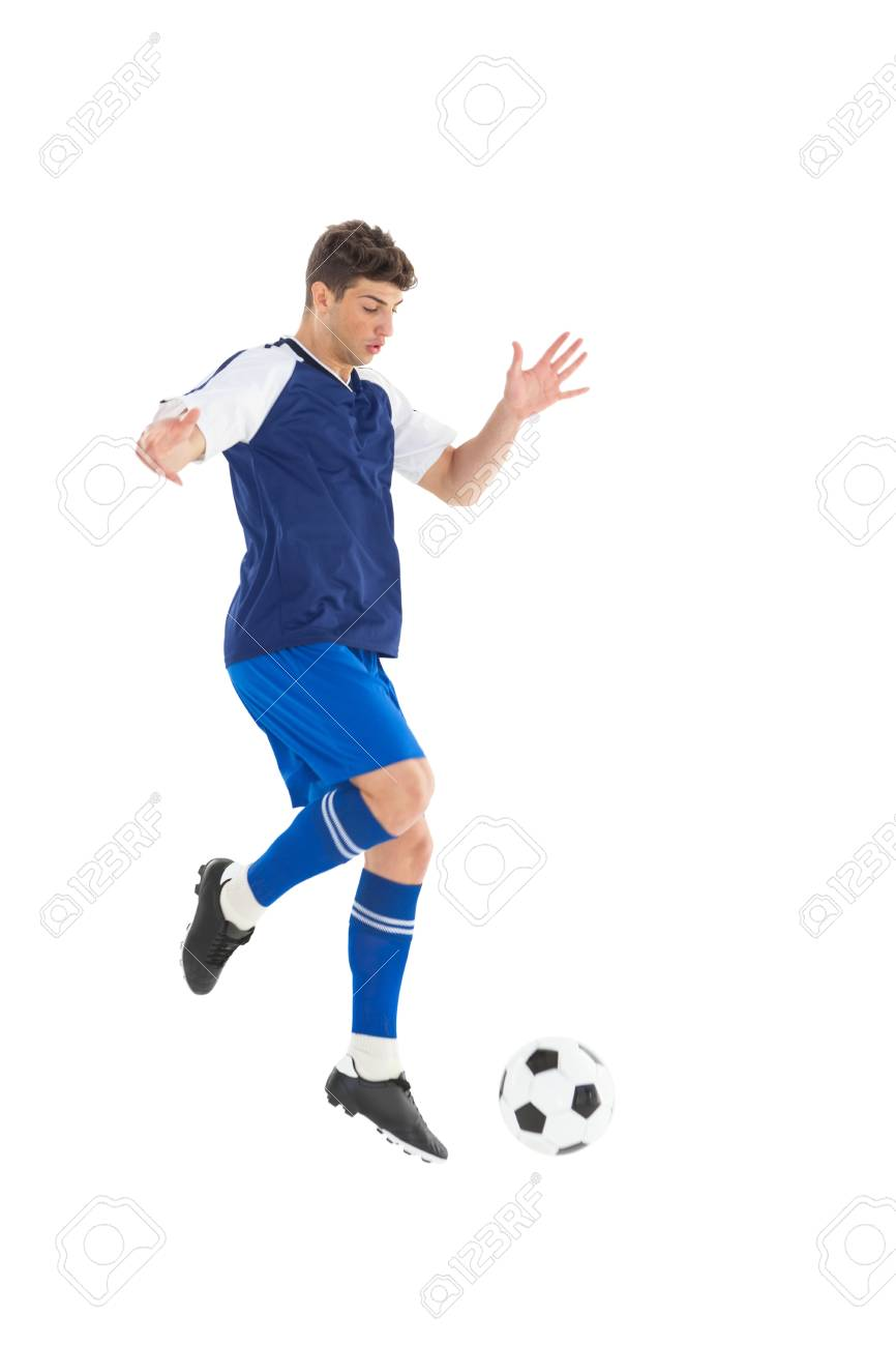 e8004e409 Football player in blue jersey kicking ball on white background Stock Photo  - 30885982