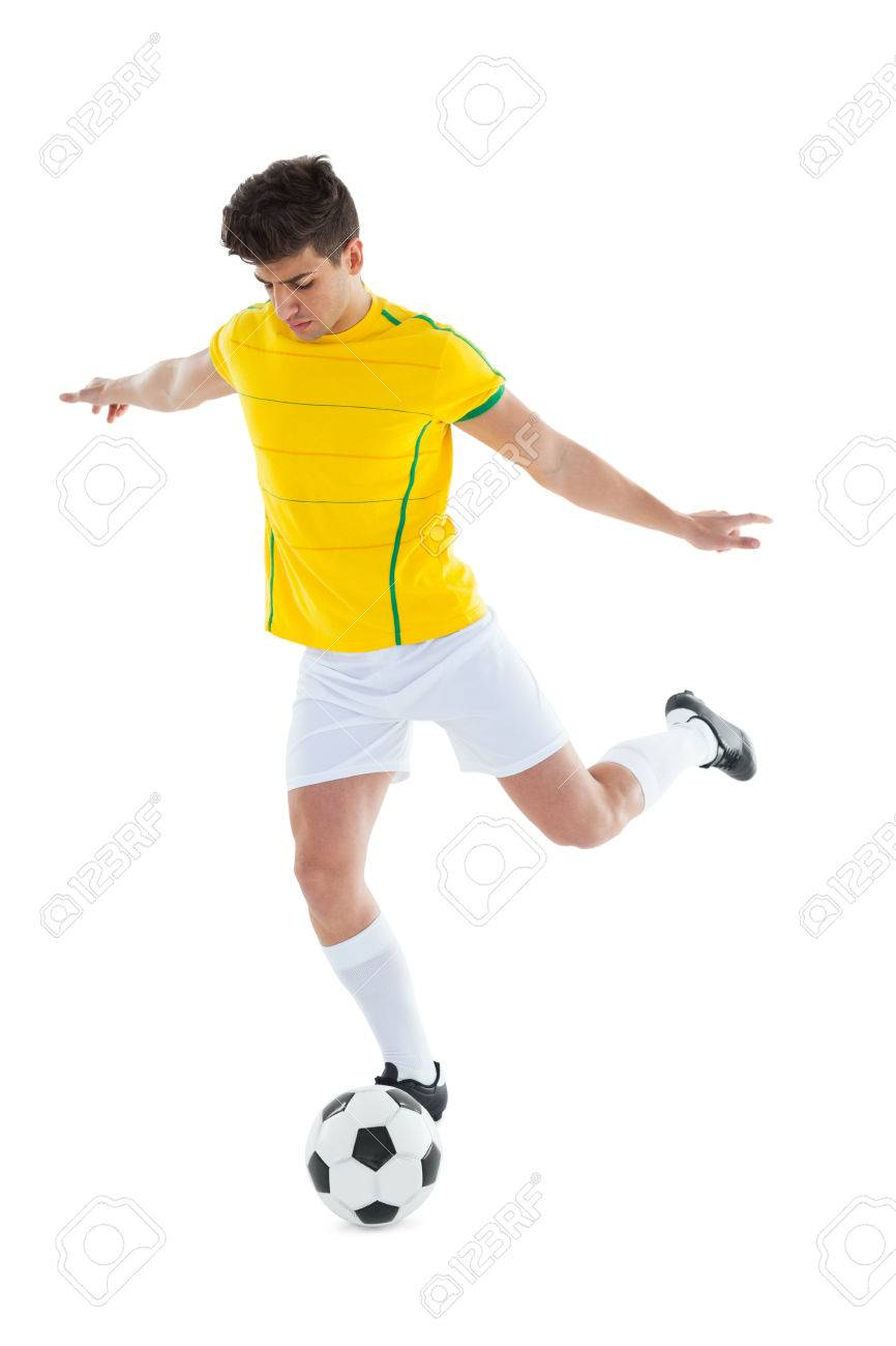 7c64647d6 Football player in yellow jersey kicking ball on white background Stock  Photo - 30922335