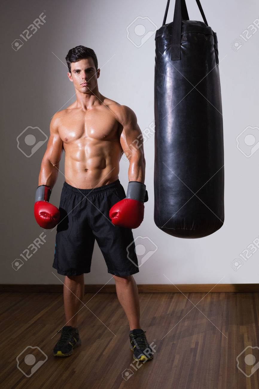 Full Length Of A Shirtless Muscular Boxer With Punching Bag In Gym Stock Photo