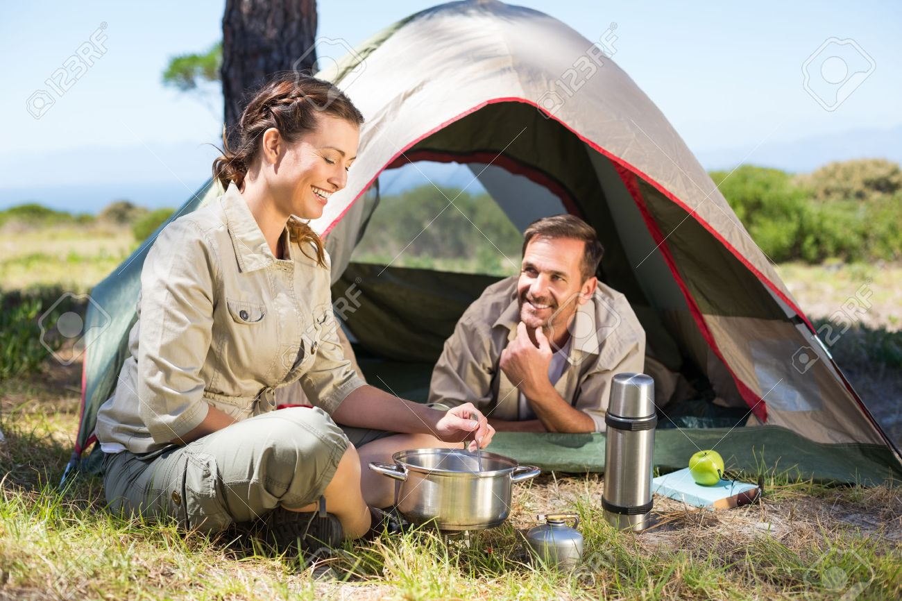 Outdoorsy couple cooking on c&ing stove outside tent on a sunny day Stock Photo - 30984718  sc 1 st  123RF.com & Outdoorsy Couple Cooking On Camping Stove Outside Tent On A Sunny ...
