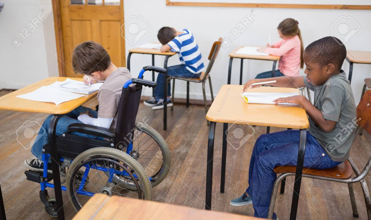 Wondrous Disabled Pupil Writing At Desk In Classroom At The Elementary Beutiful Home Inspiration Ommitmahrainfo