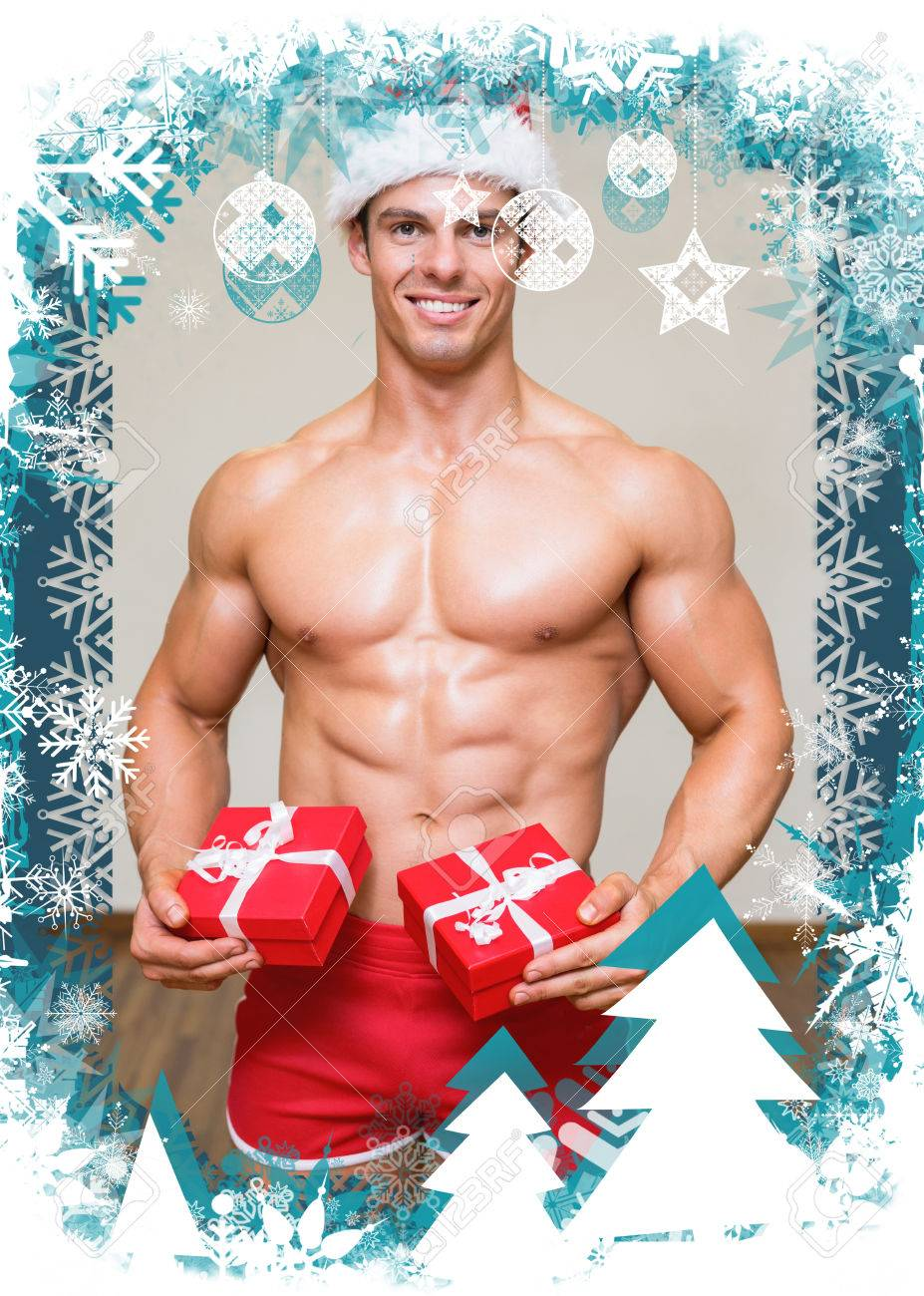 Shirtless Macho Man In Santa Hat Holding Gifts Against Christmas ...