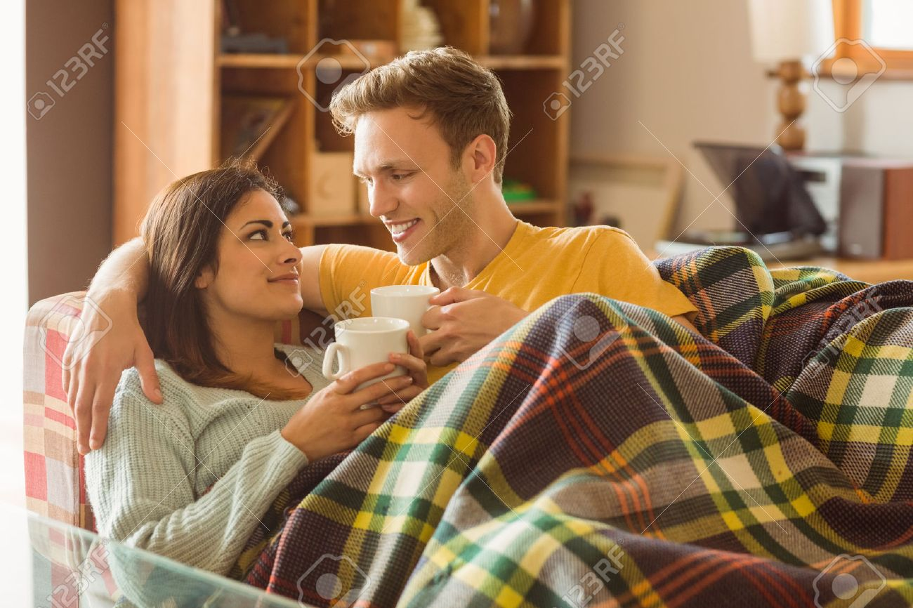 Young Couple Cuddling On The Couch Under Blanket At Home In