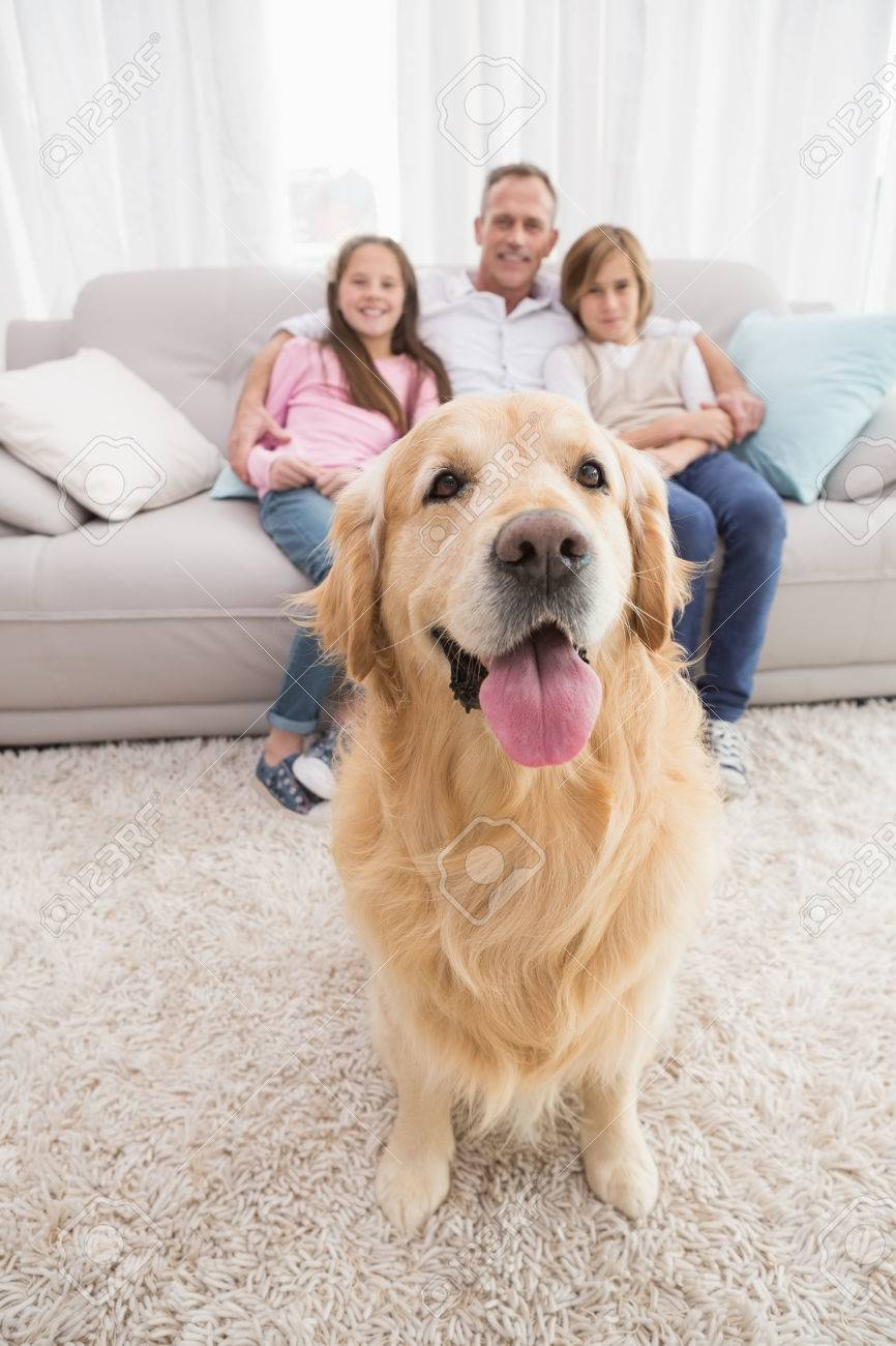 Family Sitting On The Couch With Golden Retriever In Foreground