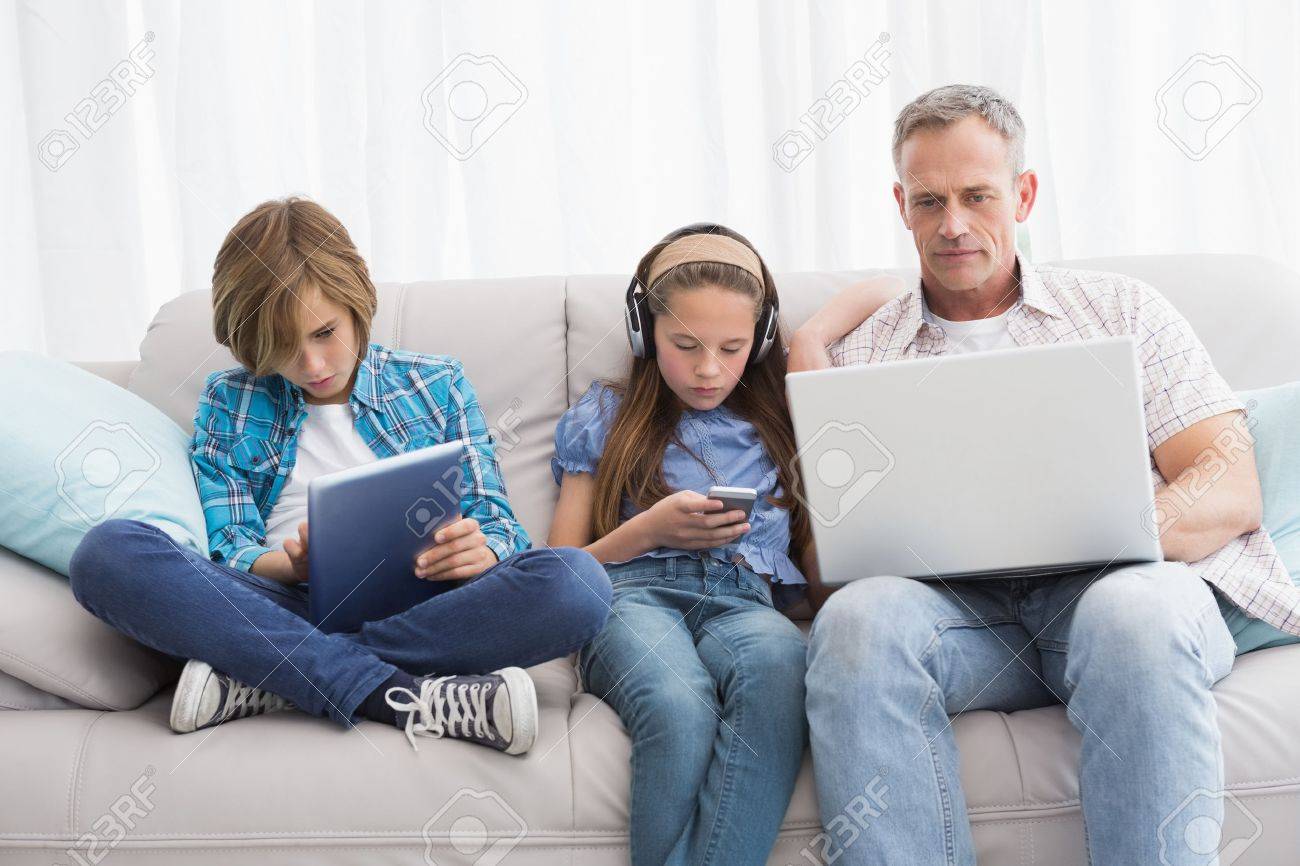 Family Focus On Wireless Technology At Home In The Living Room Stock Photo    31892810