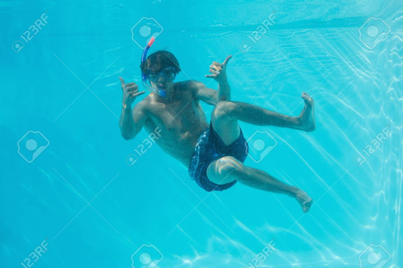 full length of a young man wearing snorkel underwater stock photo