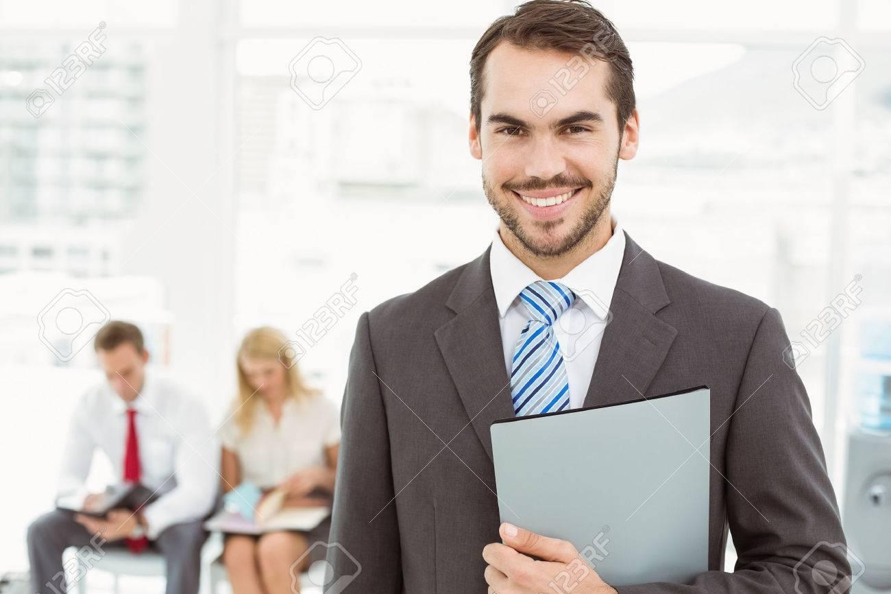 portrait of businessman against people waiting for job interview portrait of businessman against people waiting for job interview in office stock photo 32789325