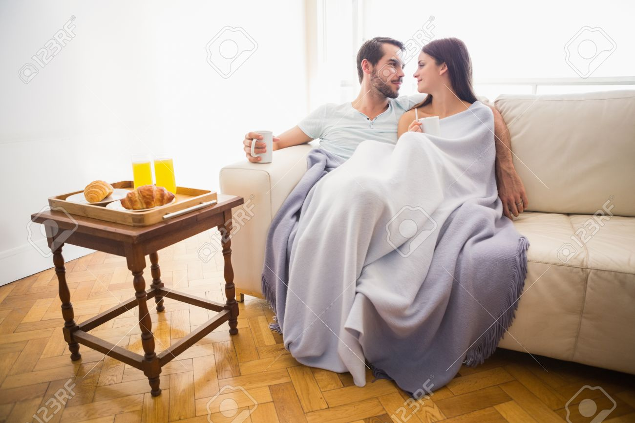 Cute Couple Relaxing On Couch Under Blanket At Home In The Living Room Stock Photo