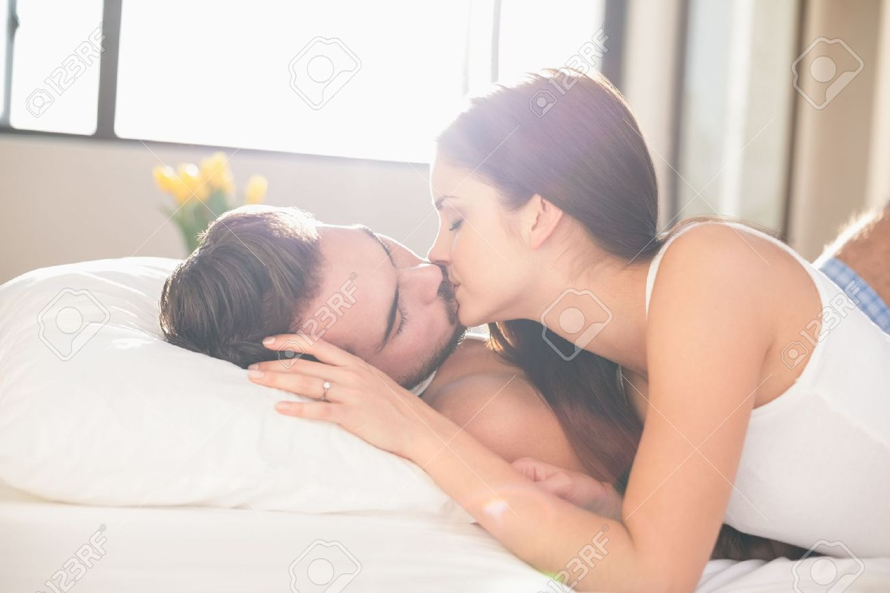 Stock Photo   Young Couple Kissing In Bed At Home In Bedroom