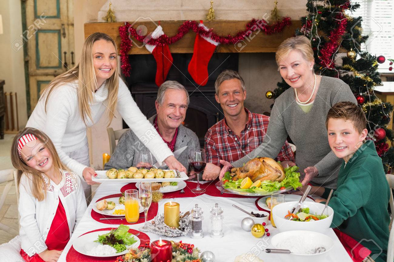 Two Women Serving Christmas Dinner To Their Family At Home In The Living Room Stock Photo