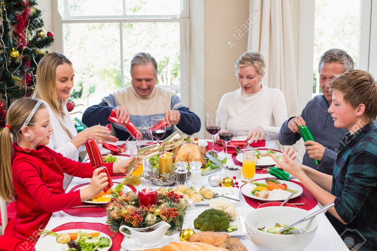 Family Pulling Christmas Crackers At The Dinner Table Home In Living Room Stock Photo