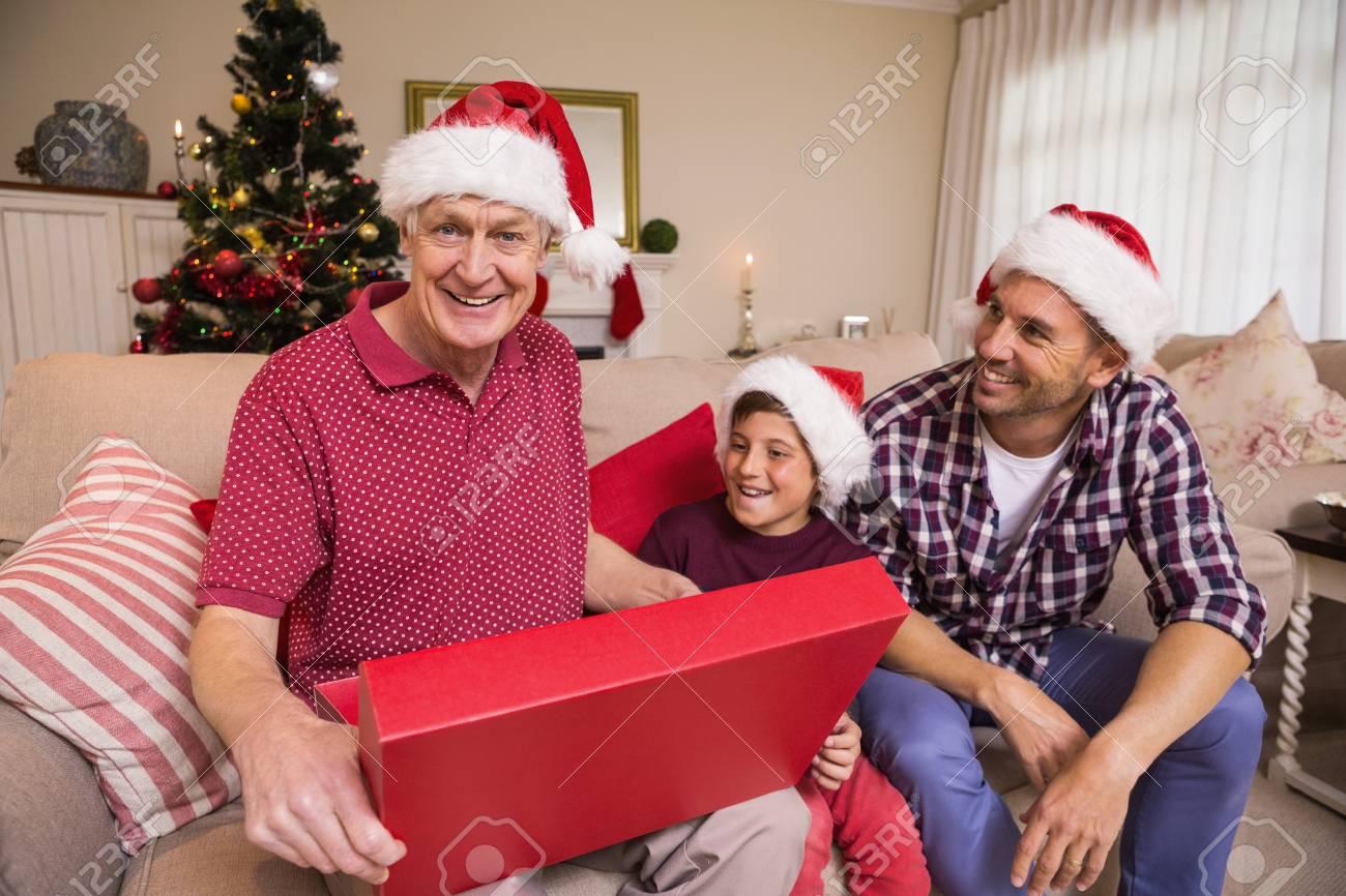 grand-père souriant ouvrir son cadeau à la maison dans le salon