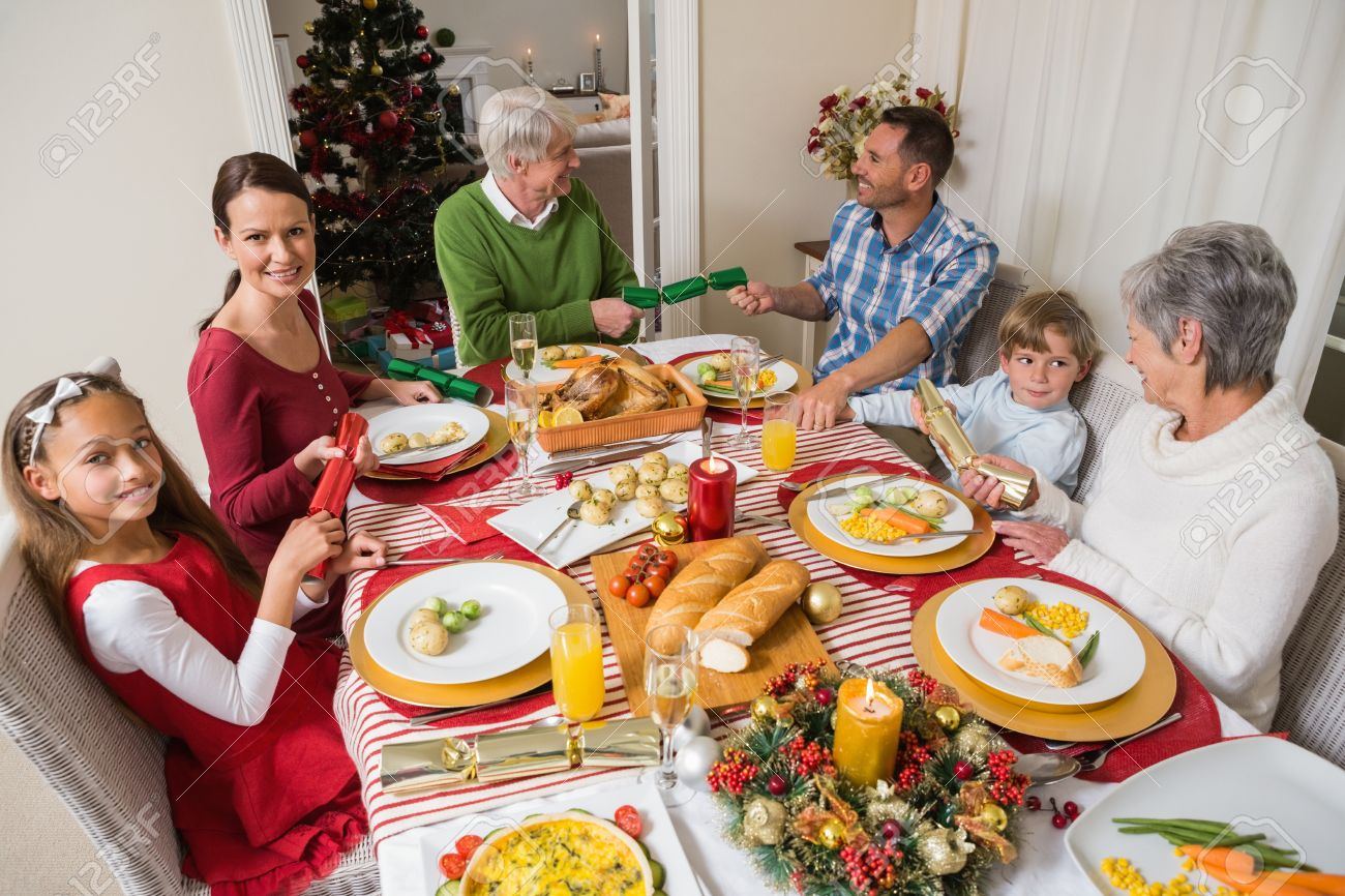 Smiling Family Pulling Christmas Crackers At The Dinner Table Home In Living Room Stock