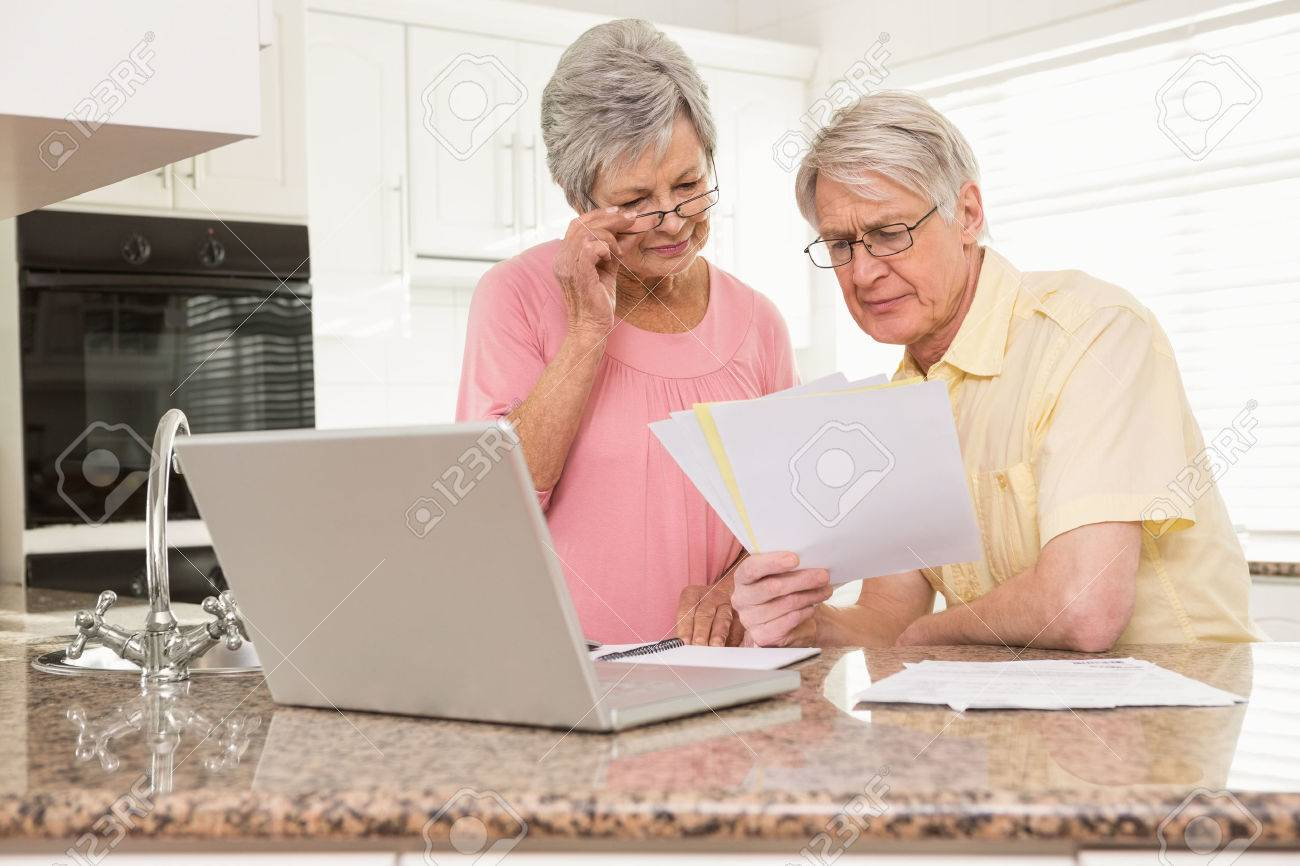 Senior couple paying their bills with laptop at home in the kitchen - 33941183