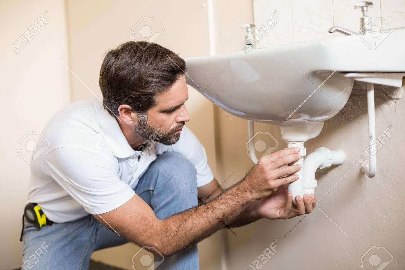 Plumber Fixing The Sink In A Bathroom In A New House Stock Photo   33941404