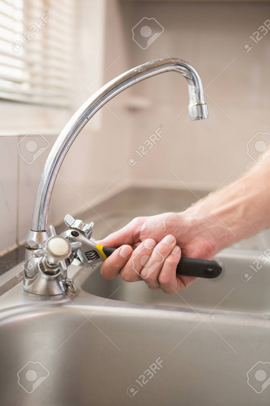 Man Fixing Tap With Pliers At Home In The Kitchen Stock Photo ...