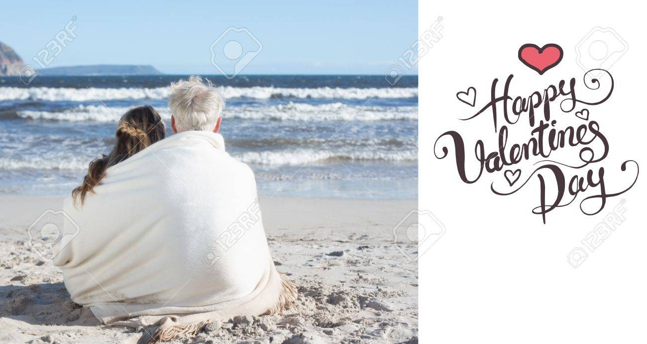 Couple Sitting On The Beach Under Blanket Looking Out To Sea Stock