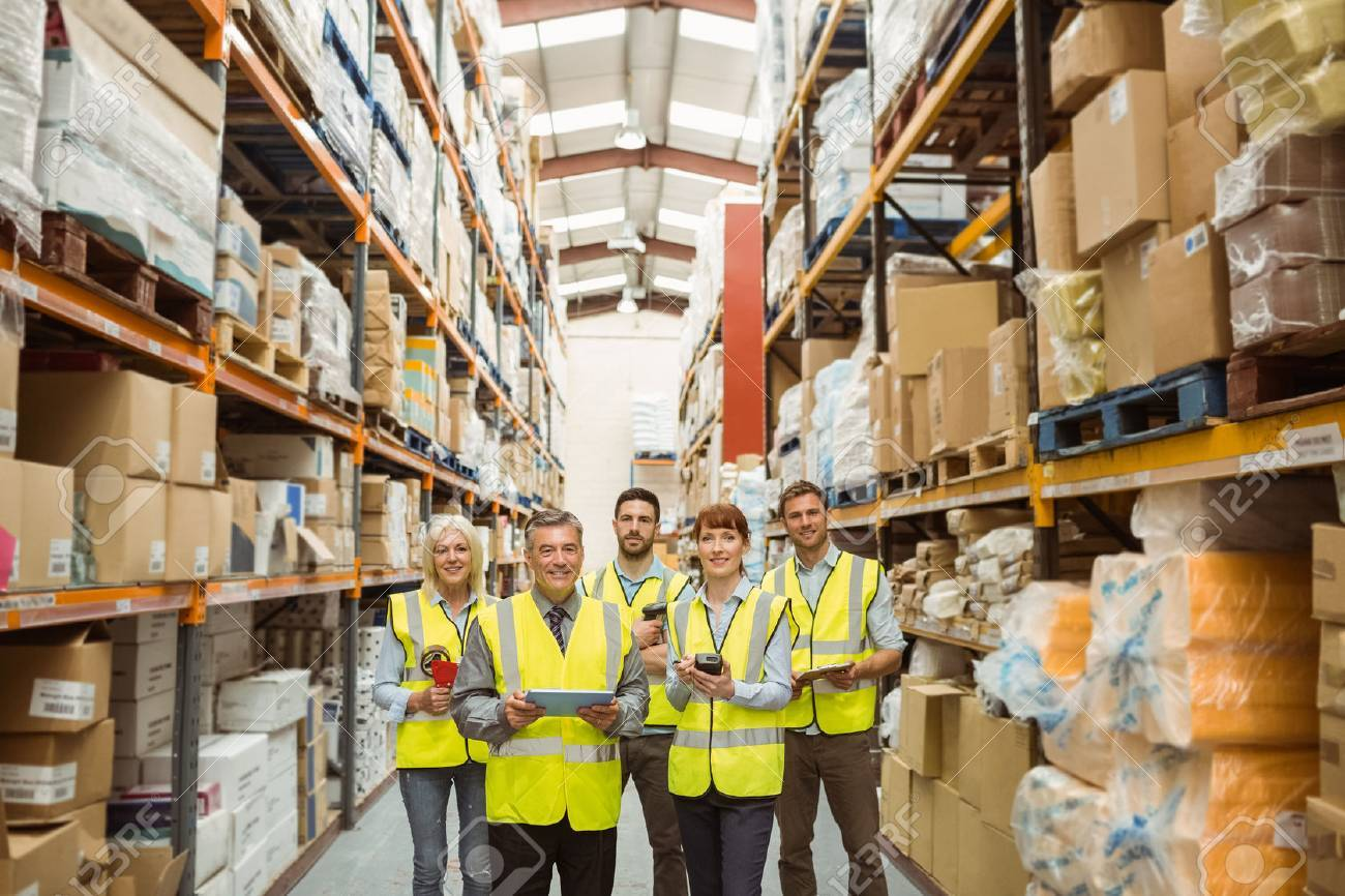 smiling warehouse team looking at camera in a large warehouse stock