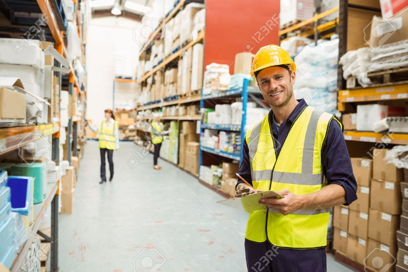 Warehouse worker smiling at camera with clipboard in a large warehouse worker smiling at camera with clipboard in a large warehouse stock photo 46210302 sciox Choice Image