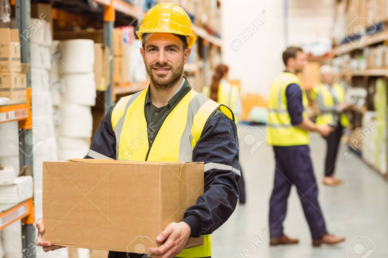 warehouse worker smiling at camera carrying a box in a large stock