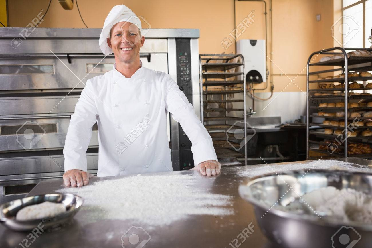 Smiling Baker Standing Behind The Counter In The Kitchen Of The ...
