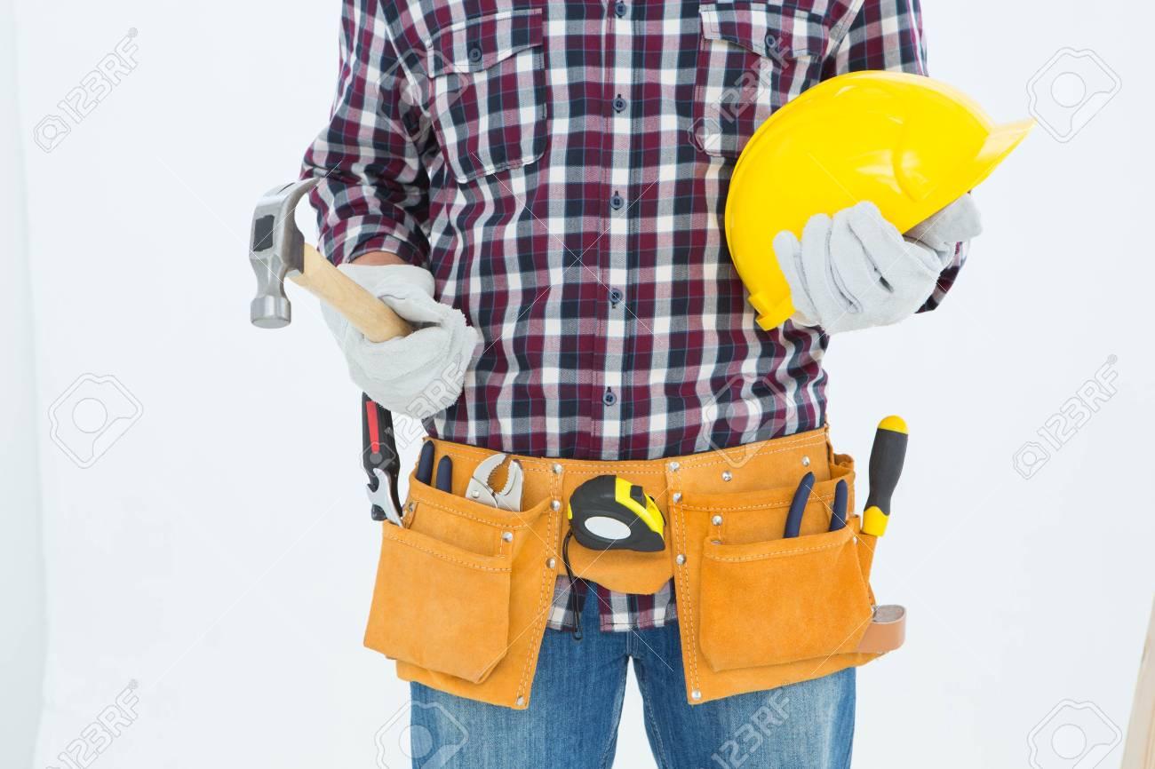 32c133a7ac91 Banque d images - Image recadrée bricoleur port de la ceinture de l outil  tout en maintenant un casque et un marteau sur fond blanc