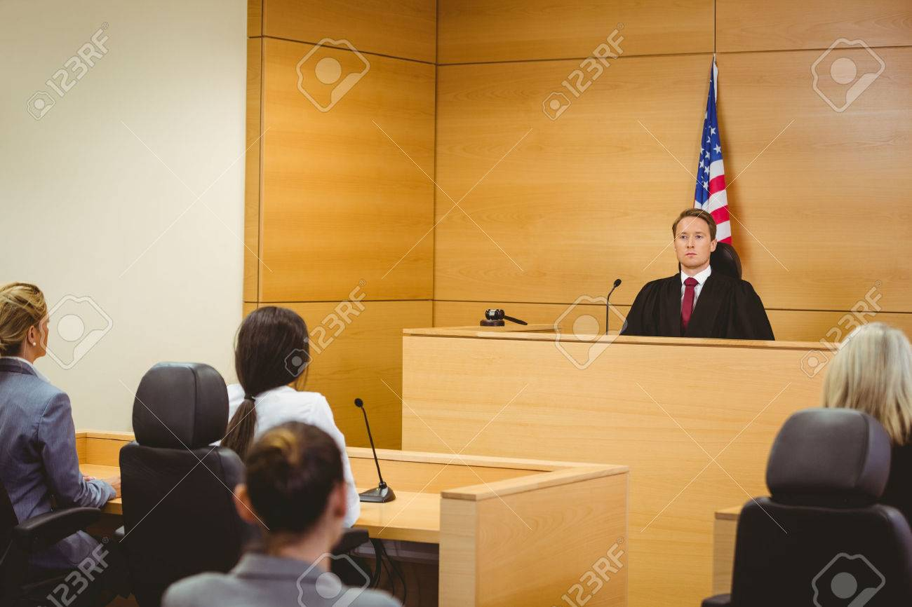 Unsmiling judge with american flag behind him in the court room - 36417391