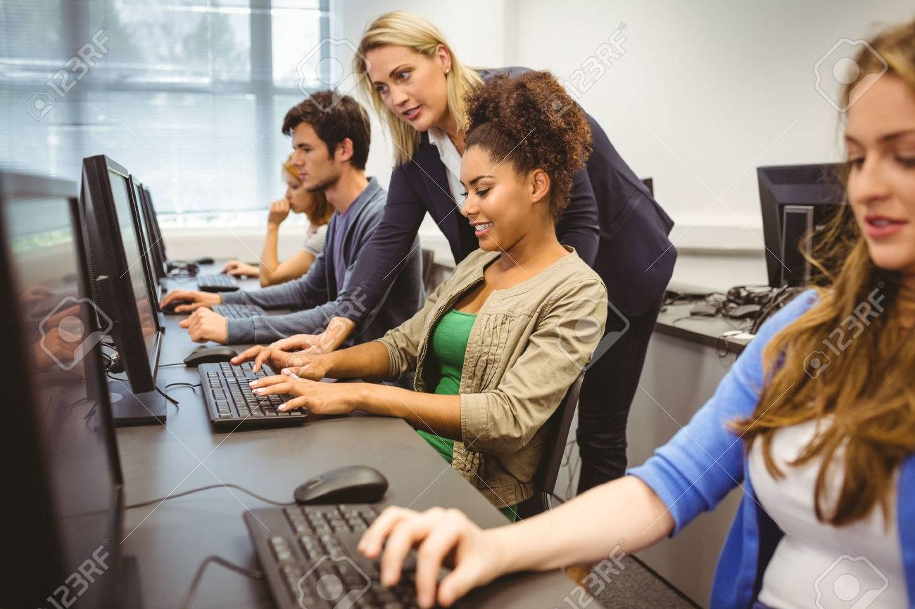 Attractive teacher helping her student in computer class at the university Stock Photo - 36404022