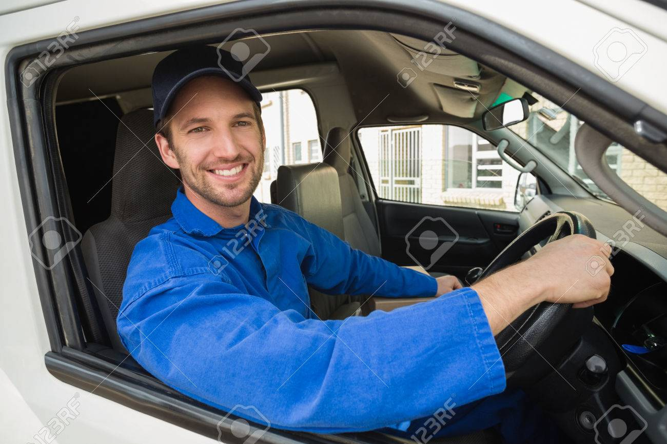 Delivery driver smiling at camera in his van outside the warehouse - 36390332