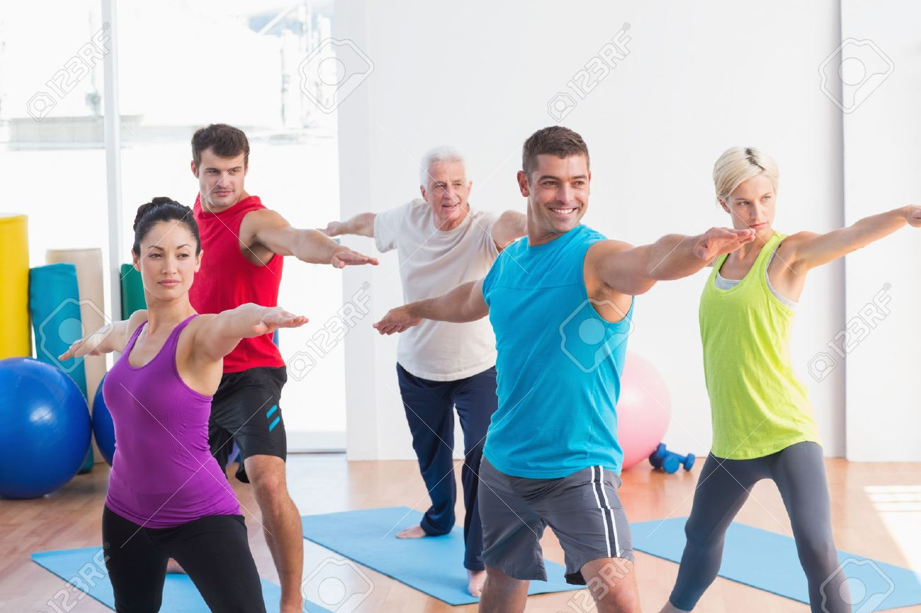 Fit Men And Women Doing Warrior Pose In Yoga Class Stock Photo