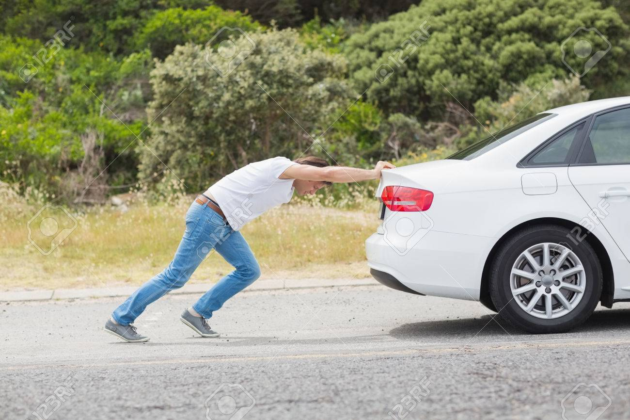 man pushing his car at the side of the road stock photo picture and