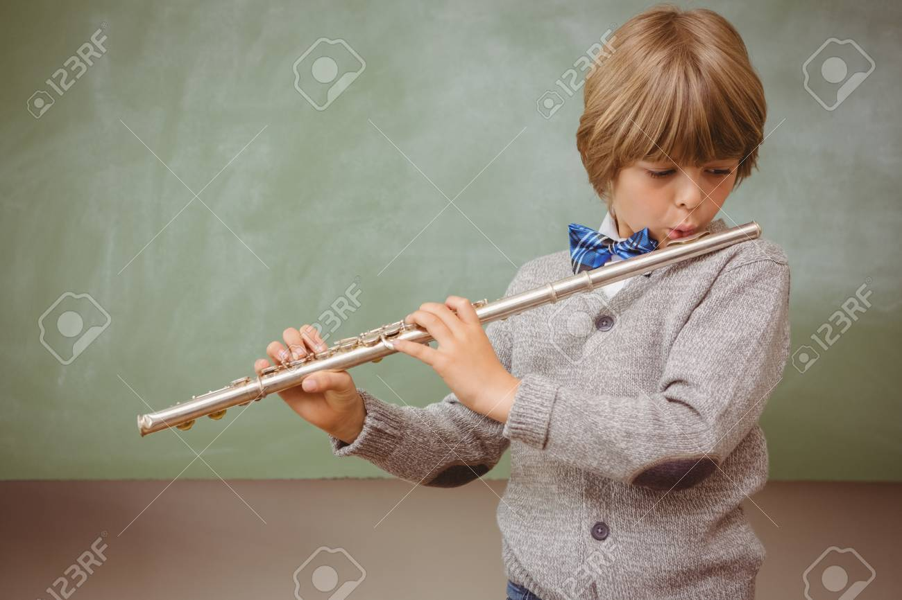 Portrait of cute little boy playing flute in classroom Stock Photo - 38133128